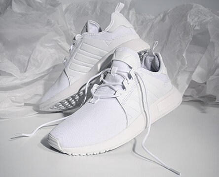 Shop shoes for women, featuring the all-white adidas Xplorer, along with styles from Vans and other top brands.